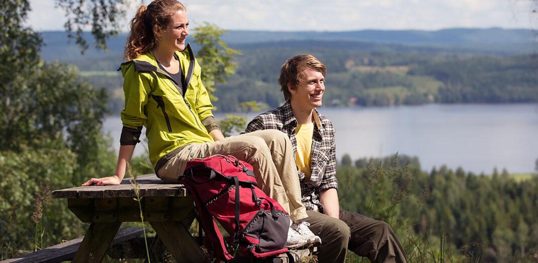 Man och kvinna som njuter av utsikt i ett skogslandskap.