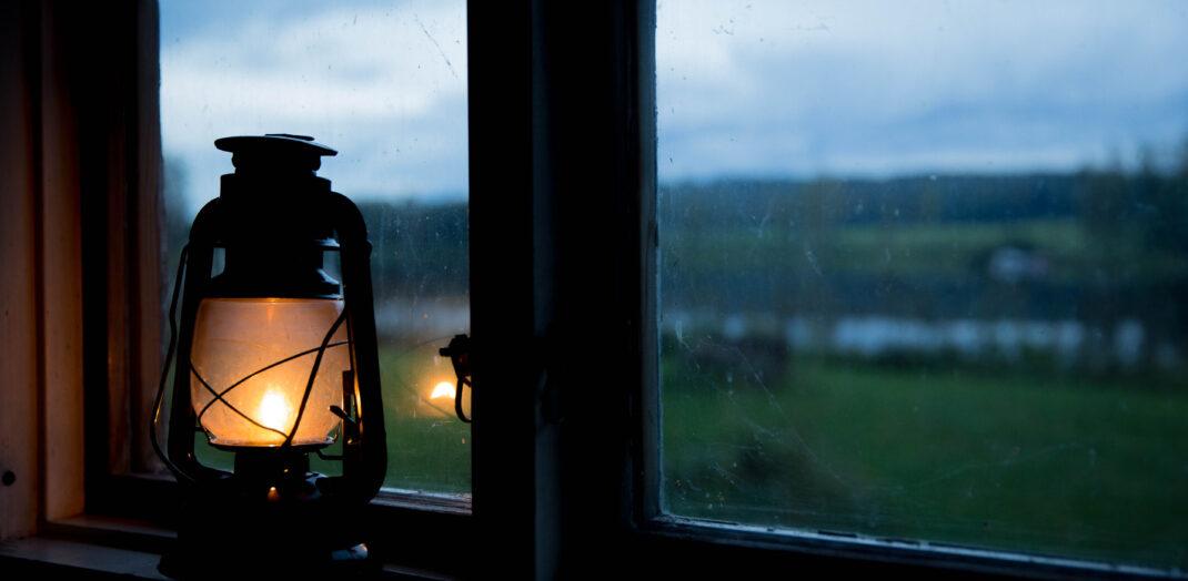 Lykta vid ett fönster som överblickar ett skogslandskap.