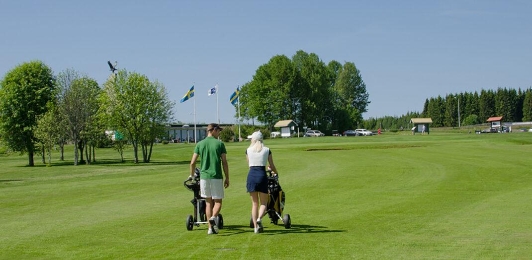 Vy över golfbana med par som promenerar.