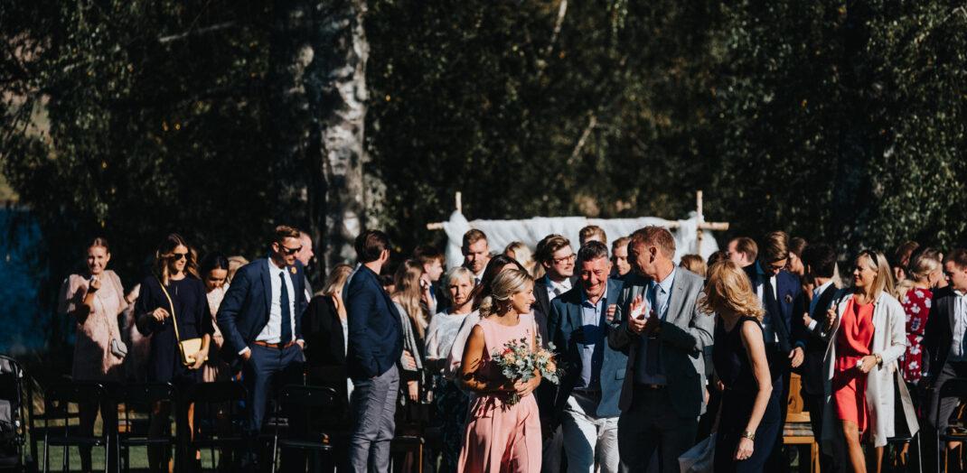 Bröllopsgäster ute på en gräsplan.