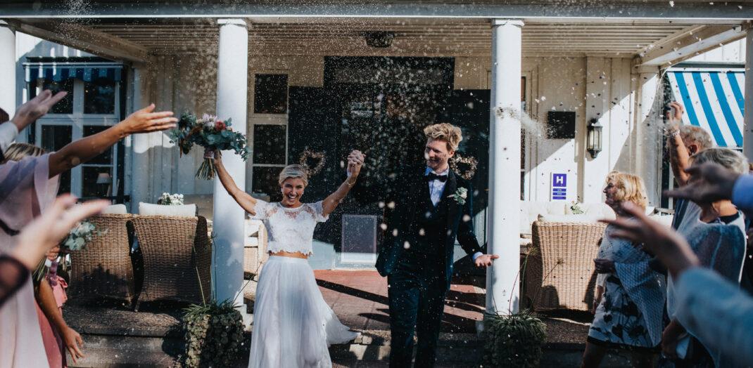Nygift brudpar som dränks i konfetti utanför herrgården.