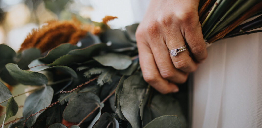 Närbild på kvinnlig hand som håller i en blombukett.