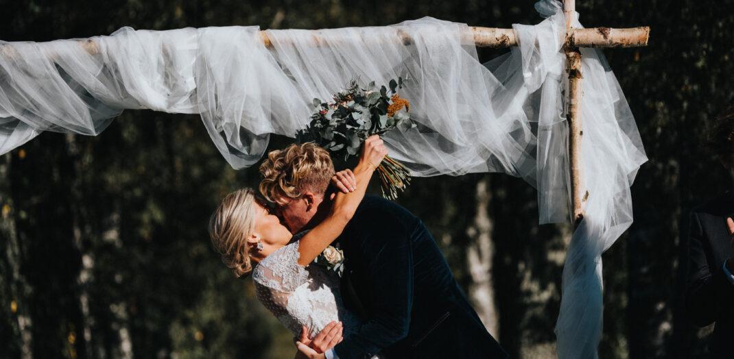 Brudpar som kysser varandra under ett vitt skynke.