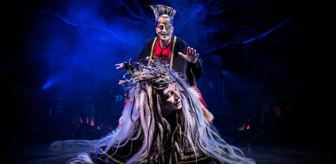 Teaterscen med en man som håller i ett huvud.