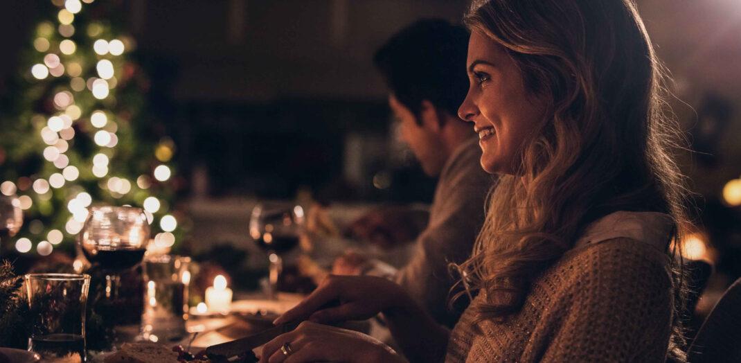 Kvinna som äter julmat i ett stämningssfullt ljus.