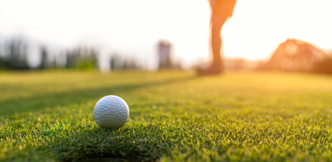 Närbild på golfboll som är på väg in i hålet.