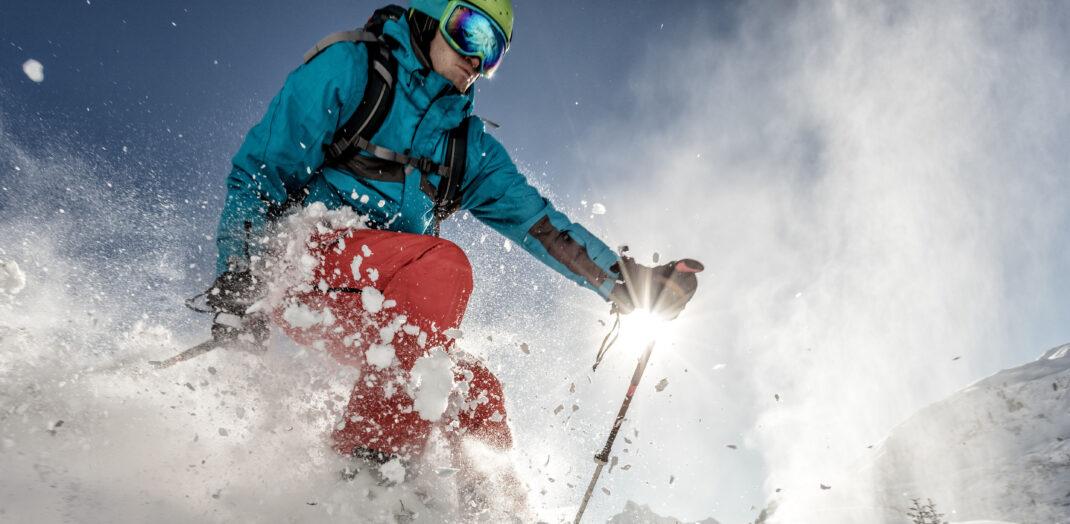 Skidåkare som åker ner för backe med snö som yr.