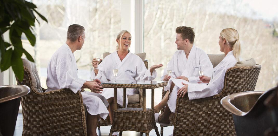 Fyra personer i badrockar sitter vid ett bord.