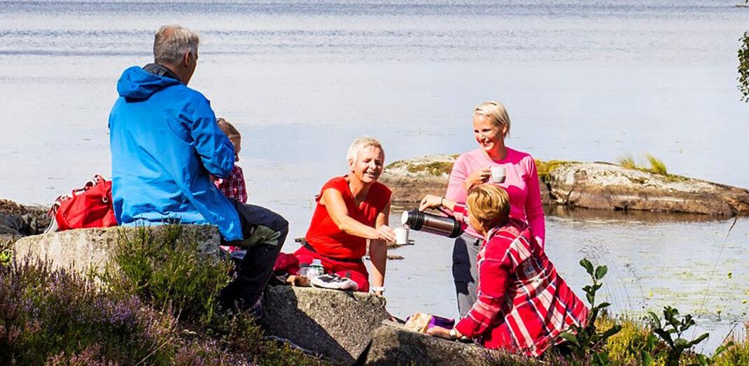 En familj som fikar på en klippa vid vattnet.