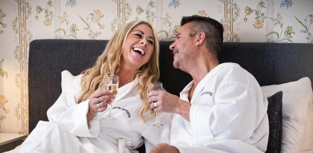 Par i badrock som ligger i en säng och skrattar.