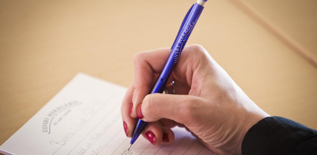 Närbild på hand som skriver på papper.