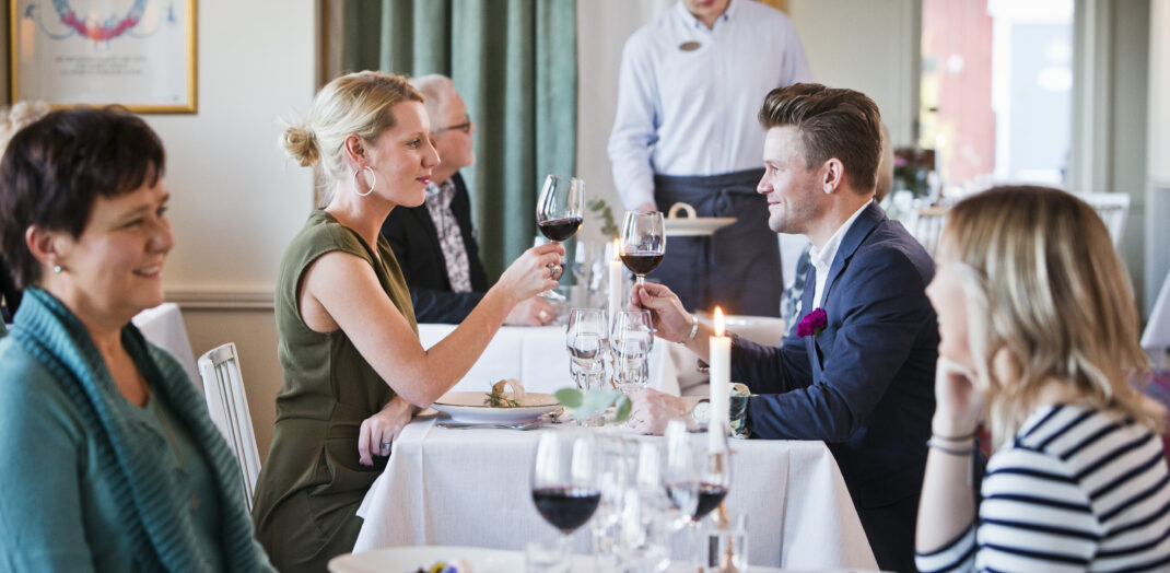 Matgäster vid ett uppdukat matbord.